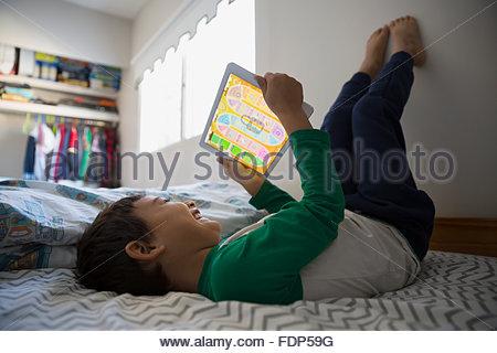 Junge Füße mit digital-Tablette auf Bett - Stockfoto