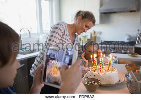 Mutter und Kinder fotografieren Geburtstagstorte mit Kerzen - Stockfoto