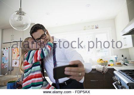Vater und Tochter küssen nehmen Selfie in Küche - Stockfoto