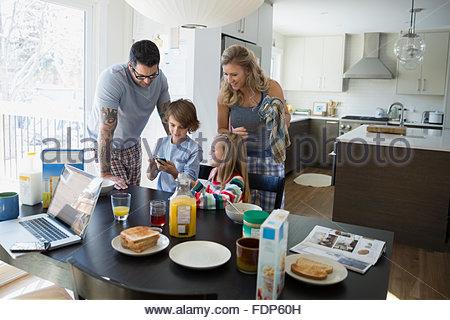 Familie Blick auf Handy am Frühstückstisch - Stockfoto