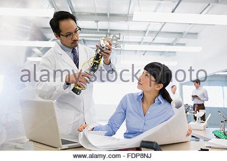 Ingenieure mit Blaupausen Prüfung Robotik - Stockfoto