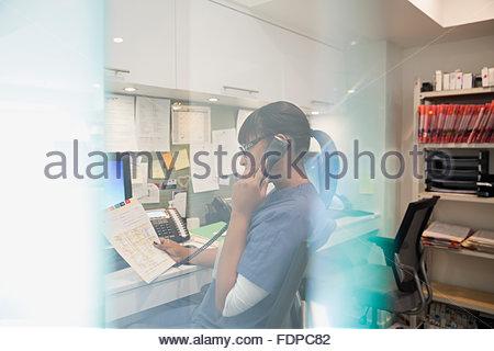 Krankenschwester am Telefon an Krankenschwestern Station sprechen - Stockfoto