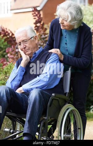 Deprimiert Senior Mann im Rollstuhl geschoben von Frau - Stockfoto