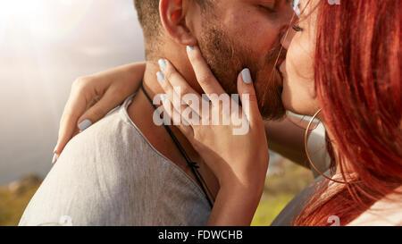 Schuss von liebevollen jungen Paar küssen im freien hautnah. Mann und Frau küssen einander romantisch Suche sehr verliebt.