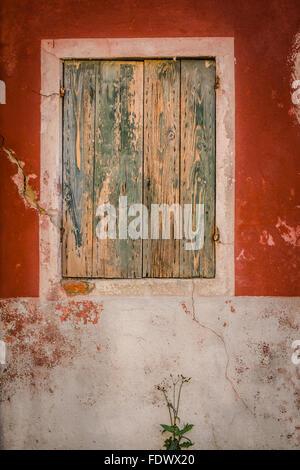 Eine grüne Peeling bemalten Fensterläden Fenster in einem rot lackierten niedergehenden Wand gesetzt. Burano, Italien. - Stockfoto