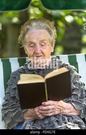 Eine ältere Frau liest das Buch in der Laube sitzen. - Stockfoto