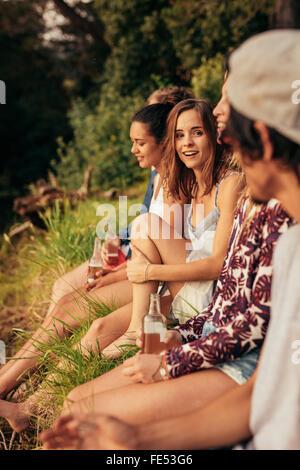 Porträt der jungen Frau sitzt mit ihren Freunden an einem See. Junge Menschen hängen am See. - Stockfoto