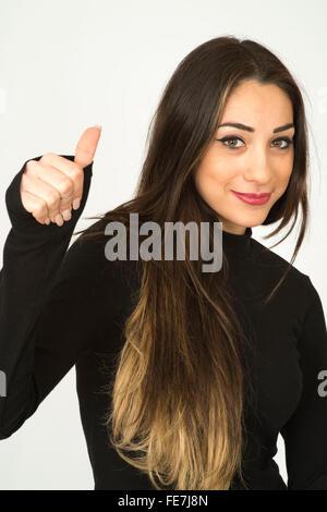 Attraktive zuversichtlich erfolgreichen jungen Frau geben ein positives Daumen nach oben Handbewegung - Stockfoto