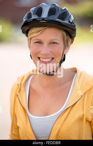 Frau mit einem Fahrradhelm auf dem Kopf, Porträt - Stockfoto