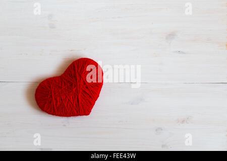 Rotes Herzform aus Wolle auf weißem Hintergrund aus Holz hergestellt. Bild der Valentinstag - Stockfoto