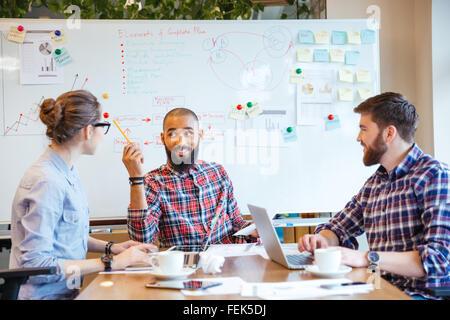 Multiethnische Gruppe junger Leute sitzen im Konferenzraum und brainstorming auf Business-meeting - Stockfoto