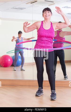 Zwei Frauen in Führungspositionen mit Hula Hoops in der Turnhalle - Stockfoto