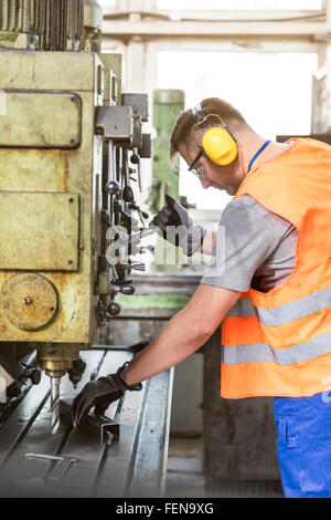 Arbeiter in Schutzkleidung, die Bedienung von Maschinen im Werk - Stockfoto