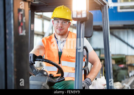 Porträt-Arbeiter fahren Gabelstapler in Fabrik - Stockfoto