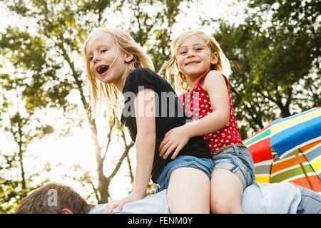 Reifer Mann mit zwei jungen Töchter Huckepack im park - Stockfoto