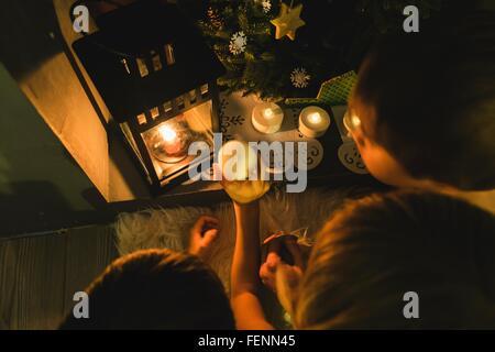 Draufsicht der Mutter und zwei Söhne Vorbereitung Weihnachtskerzen im Kamin - Stockfoto