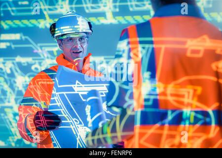 Ingenieure mit Blaupausen und projizierte Pläne - Stockfoto