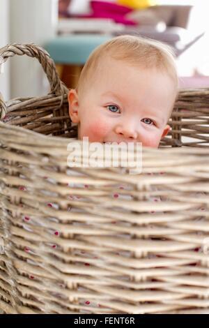 Porträt von netten weiblichen Kleinkind versteckt im Weidenkorb - Stockfoto