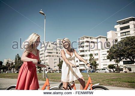 Junge Frauen, die zu Fuß mit dem Fahrrad vorbei an Gebäuden, Kapstadt, Südafrika - Stockfoto