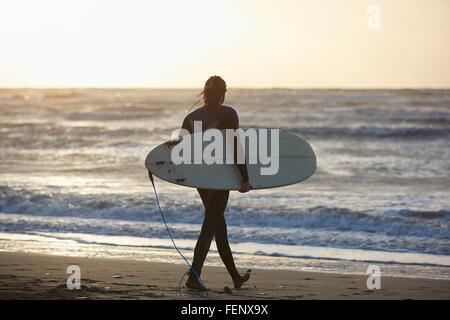 Junge männliche Surfer zu Fuß am Strand tragen Surfbrett, Devon, England, UK - Stockfoto