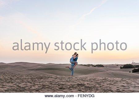 Mitte erwachsenen Mannes geben Freundin eine Huckepack auf Düne, Maspalomas, Gran Canaria, Kanarische Inseln, Spanien - Stockfoto