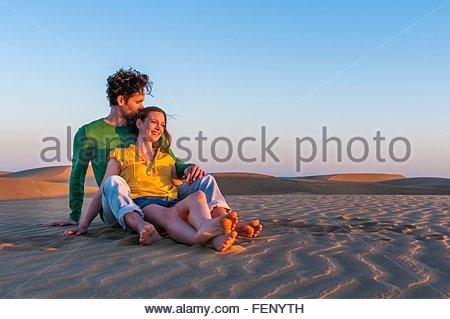 Romantische Mitte erwachsenes paar sitzen auf Sanddünen bei Sonnenuntergang, Maspalomas, Gran Canaria, Kanarische - Stockfoto