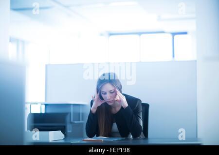 Junge Frau sitzt am Schreibtisch im Büro, Kopf in Händen nach unten, betonte - Stockfoto