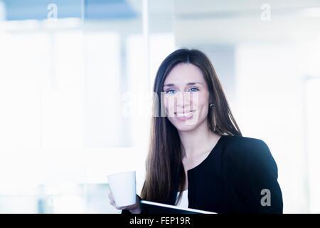 Junge Frau mit Kaffeetasse und Ringbuch Datei Blick auf die Kamera zu Lächeln - Stockfoto