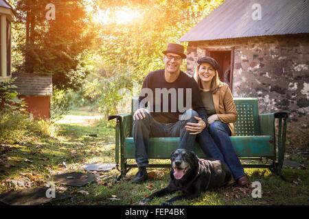 Porträt des reifes Paar mit Hund auf Bank, im Freien sitzen - Stockfoto