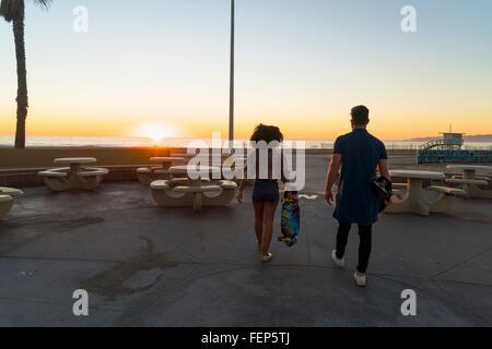 Paare, die in der Nähe von Strand, mit Skateboards, Rückansicht - Stockfoto