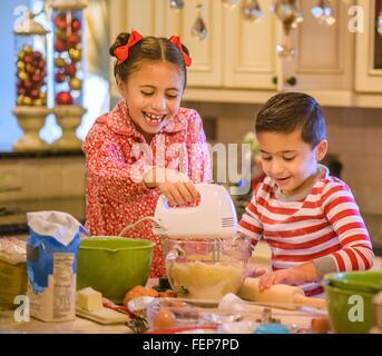 Kinder in Küche tragen Pyjama mit Handmixer auf Cookie Teig lächelnd - Stockfoto