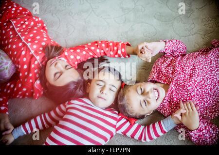 Draufsicht der Kinder tragen Pyjama auf Teppich halten Hände Augen liegen geschlossen - Stockfoto