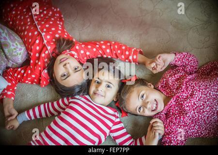 Draufsicht der Kinder tragen Pyjama liegend auf Teppich, Blick auf die Kamera zu Lächeln - Stockfoto