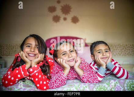 Kinder tragen Schlafanzüge an Fronten auf Bett liegend Kinn in Händen, Blick auf die Kamera zu Lächeln - Stockfoto