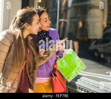 Junge weibliche Erwachsene Zwillinge Shopping Tragetaschen auf Stadt shop - Stockfoto