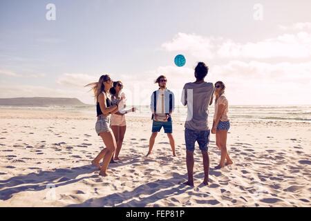 Gruppe von Jugendlichen mit Ball am Strand spielen. Junge Freunde genießen Sommerferien an einem Sandstrand.