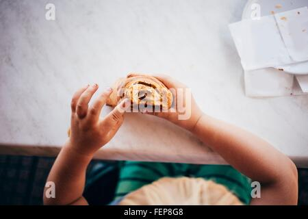 Draufsicht eines jungen an Marmor Tisch Essen Gebäck, Luino, Lombardei, Italien - Stockfoto