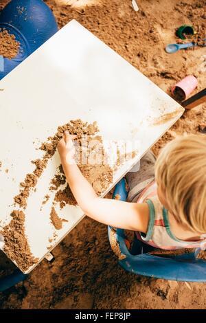 Draufsicht der Junge sitzt am Tisch im Sandkasten spielen mit sand - Stockfoto