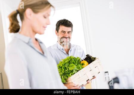 Älteres paar Vorbereitung Kiste mit frischem Gemüse in der Küche - Stockfoto