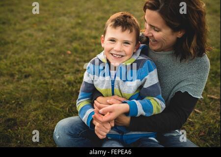 Junge sitzt auf Mütter Schoß auf Rasen, Blick auf die Kamera zu Lächeln - Stockfoto