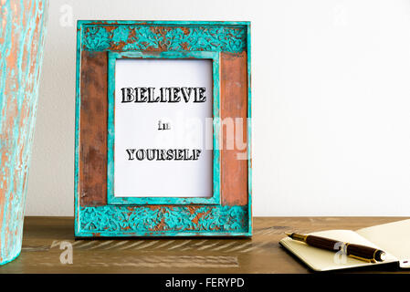 Vintage Bilderrahmen auf Holztisch über weiße Wand Hintergrund mit motivierenden Botschaft glauben IN sich selbst - Stockfoto