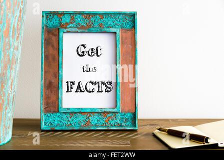 Vintage Bilderrahmen auf Holztisch über weiße Wand Hintergrund mit motivierenden Botschaft GET THE FACTS, Textfreiraum - Stockfoto