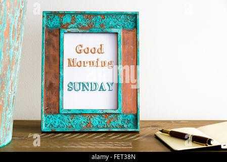 Vintage Bilderrahmen auf Holztisch über weiße Wand Hintergrund mit motivierenden Botschaft guten Morgen Sonntag - Stockfoto