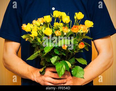 Mann hält Rosenstrauß gelb und orange. Frauen ' s Tag, Valentinstag, Muttertag. Selektiven Fokus - Stockfoto