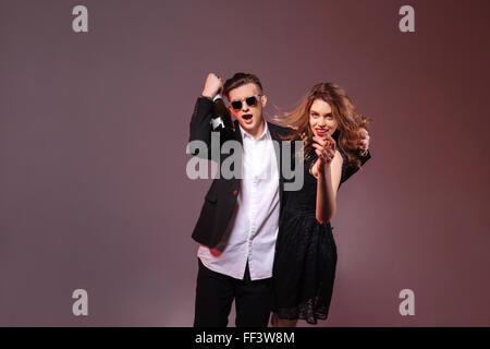 Aufgeregt, fröhliche junge Paar umarmt und Spaß mit Flasche Champagner über lila Hintergrund - Stockfoto