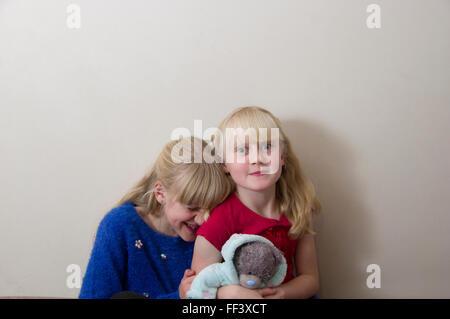 Studio-Porträt von zwei junge, blonde Mädchen vor einem weißen Hintergrund. - Stockfoto
