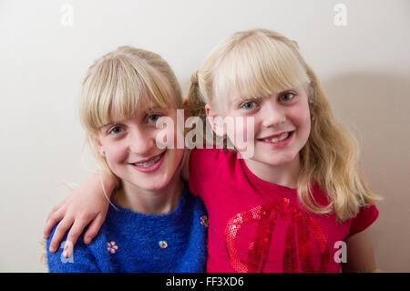 Studio-Porträt von zwei jungen, blonden Mädchen mit ihre Arme umeinander vor einem weißen Hintergrund. - Stockfoto