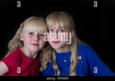 Studio-Porträt von zwei jungen, blonden Mädchen Wange an Wange vor einem schwarzen Hintergrund. - Stockfoto