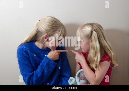 Zwei junge, blonde Mädchen aufeinander zeigen - Stockfoto