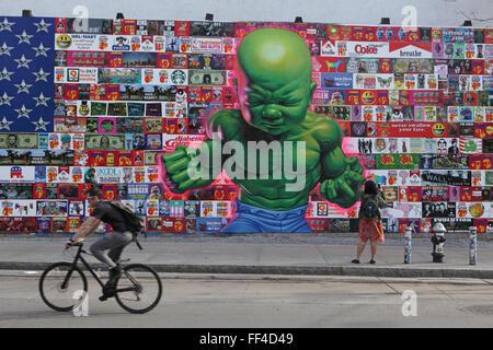 Ein Mann Zyklen um zu arbeiten vorbei ein Ron English Art Collage an der Bowery Wandbild Wand auf der Houston Street - Stockfoto